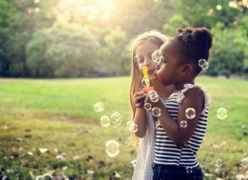 2 children playing with bubble solution outdoors