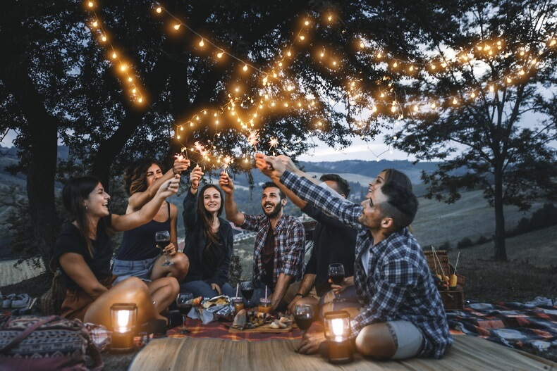 Group of friends sitting under trees raising glasses on summer evening