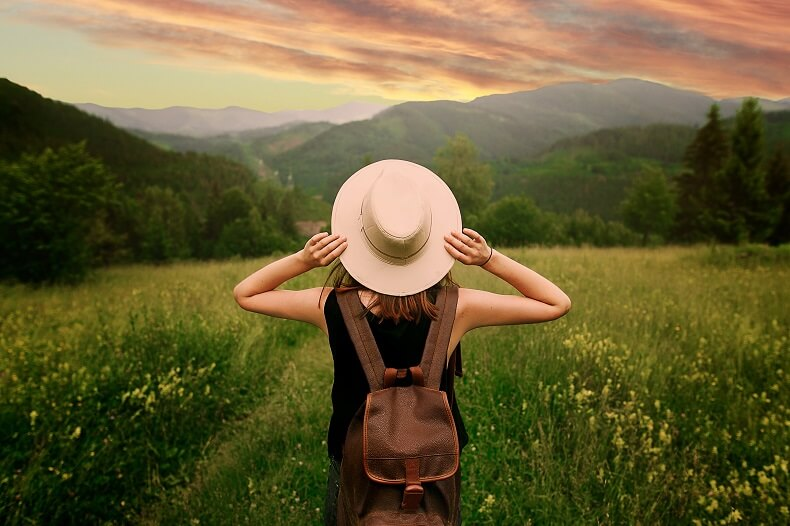 Woman with hat and backpack standing in field looking at view of mountains
